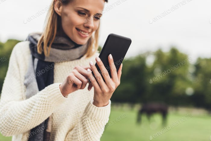 attractive woman in autumn outfit using smartphone