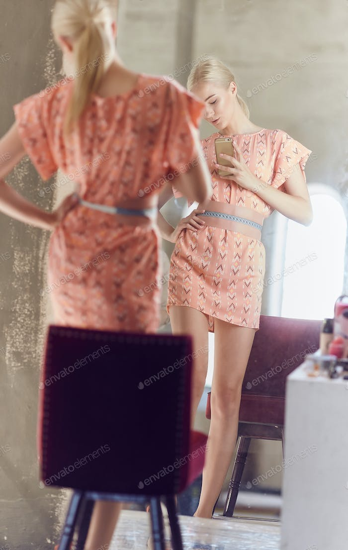 Woman poses in front of big mirror.