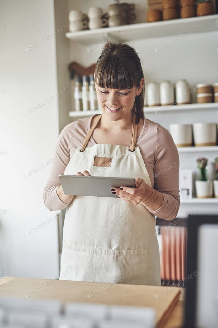 Smiling florist standing in her flower shop using a tablet