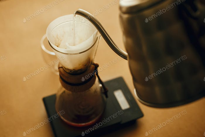Pouring hot water from steel kettle in filter with ground coffee in pour over on scale