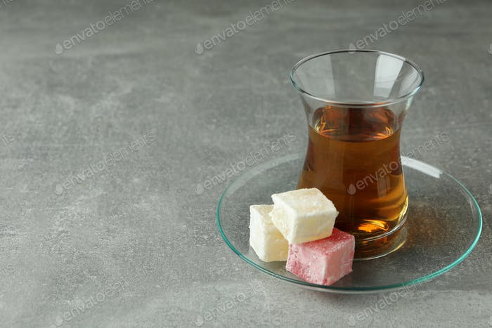 Tea and delicious turkish delight on gray background