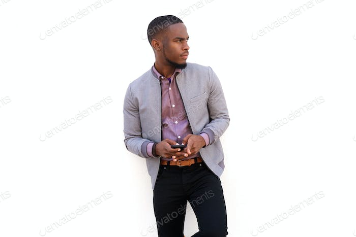Handsome african guy holding a cell phone and looking away