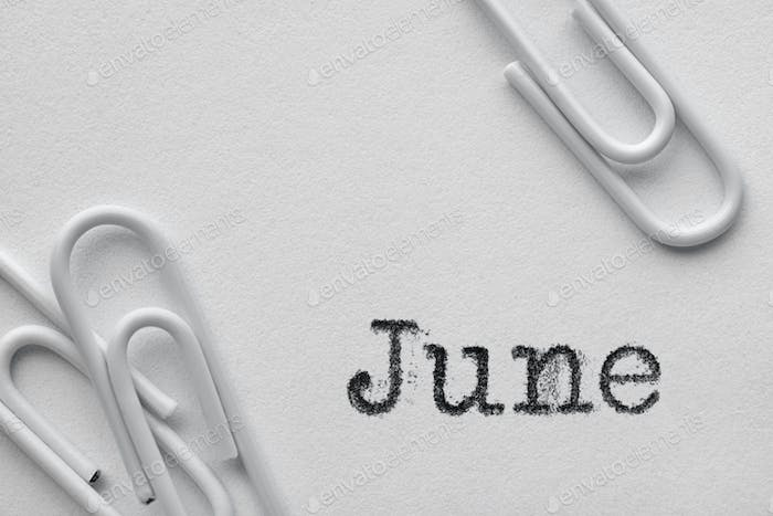 White plastic paper clips with June word