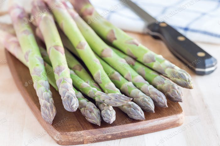 Bunch of fresh green asparagus on a wooden board, horizontal