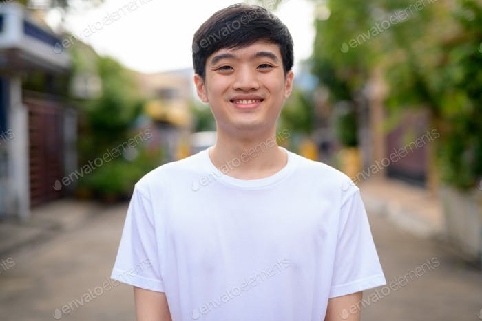 Young happy Asian man smiling in the streets outdoors