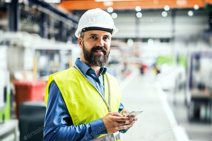 An industrial man engineer with name tag in a factory, using smartphone.