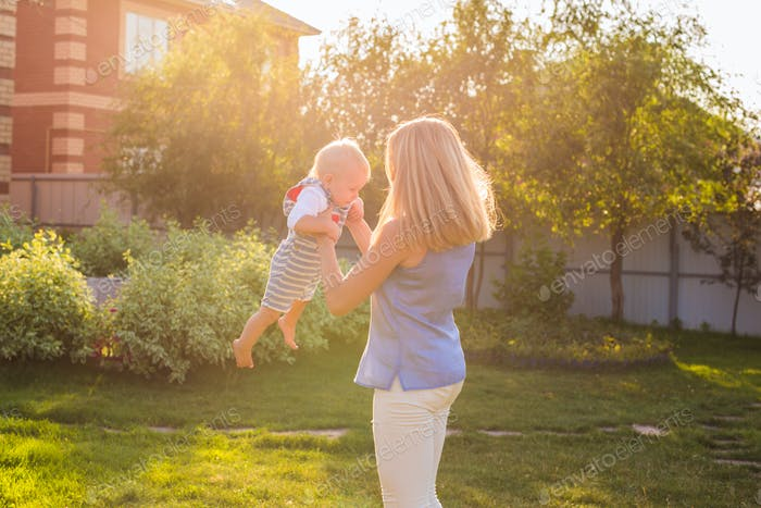 happy harmonious family outdoors. mother laughing and playing with baby in the summer on the nature