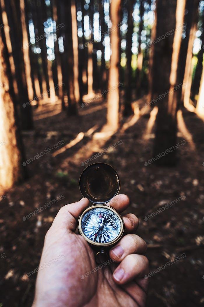 Mit einem Vintage-Kompass im Wald.