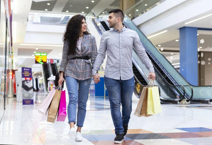 Happy millennial couple walking after shopping in mall