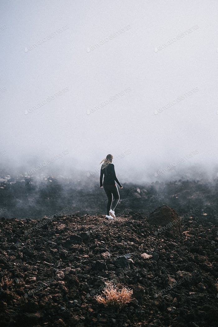 Young woman walking into the fog on a volcanic landscape on Tenerife, Canary Islands, Spain