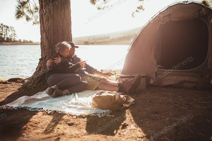 Loving senior couple camping near a lake
