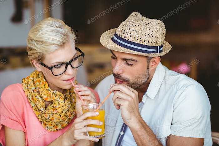 Cute couple on a date sharing an orange juice at the cafe