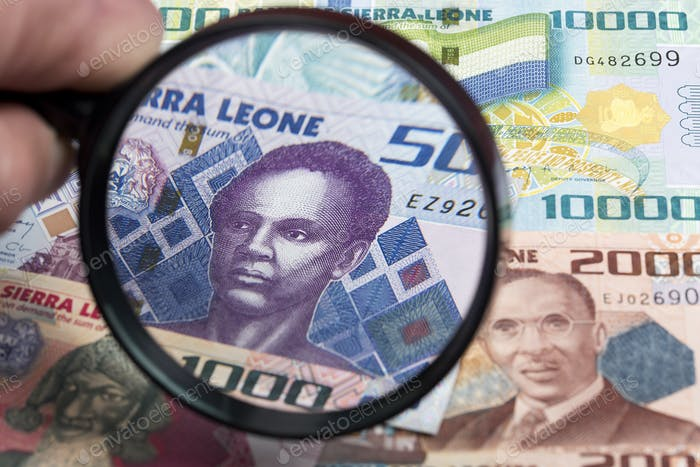 Sierra Leonean money in a magnifying glass