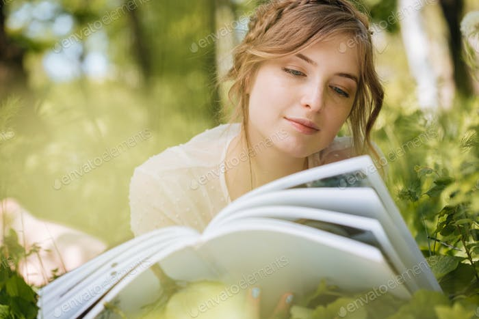 Pensive woman lying and reading magazine ourdoors