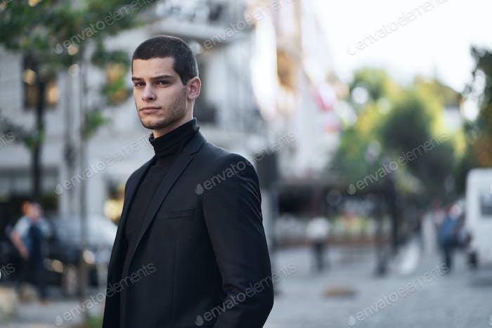 Selbstbewusster junger Mann zu Fuß auf einer europäischen Stadtstraße