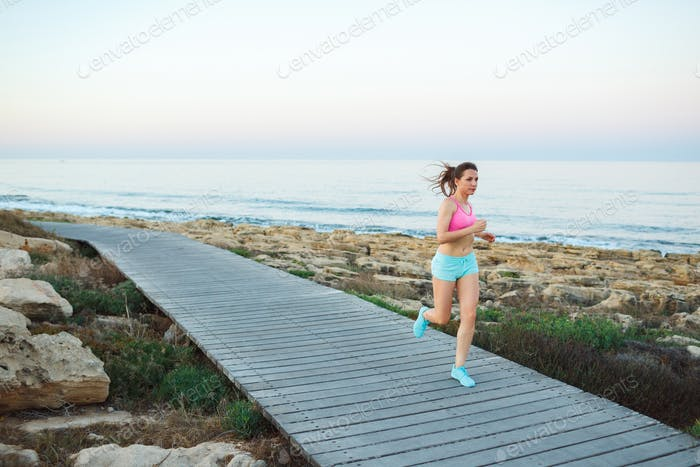 Young athletic woman running along a path by the sea