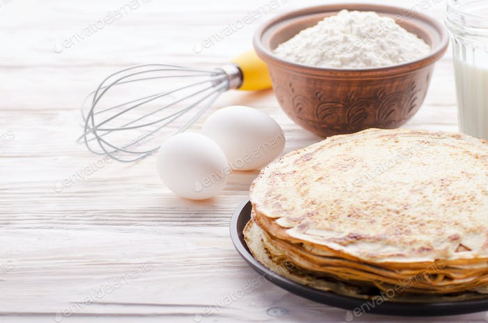 Stack of French crepes in frying pan on wooden kitchen table with milk eggs and flour aside