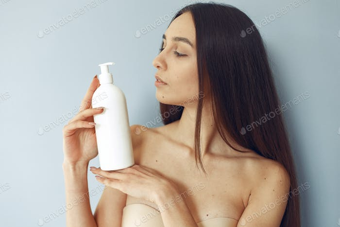 Beautiful girl standing in a studio with cream