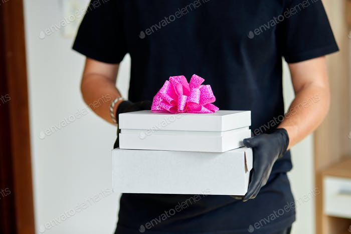 Courier man contactless delivery presents, gift box during a coronavirus epidemic.