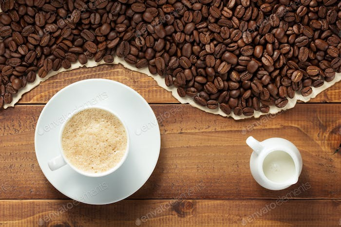 coffee beans and cup with milk on wooden background