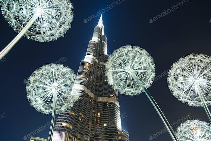 Burj Khalifa in the night against of luminous dandelions.