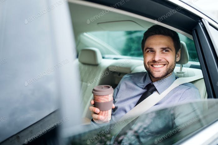 Businessman with coffee sitting on back seat in car.