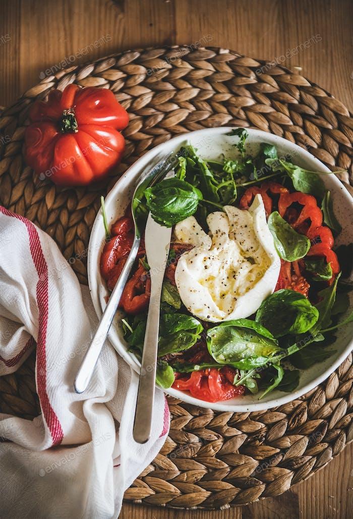 Italienischer Salat mit Buratta-Käse, Tomaten, Rucola und Basilikum