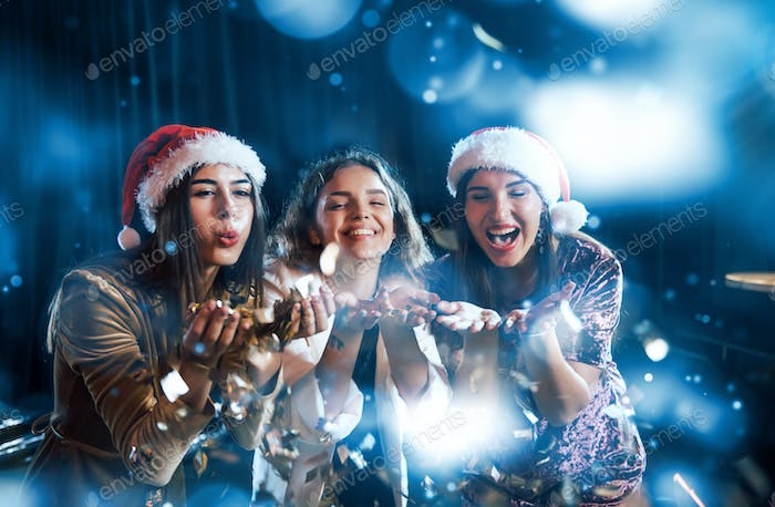 Three women blowing confetti from their hands indoors at holiday time