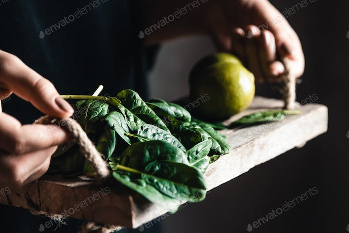 Girl holds on a vintage tray a spinach with lime. Vegan, wholesome food, eco