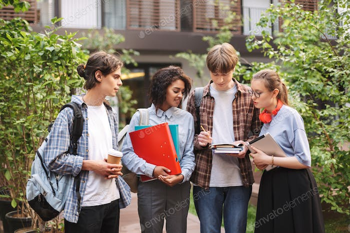 Young students standing with books and folders in hands and making notes in notebook