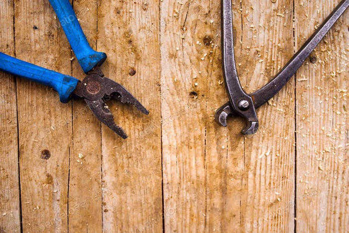 Two different pliers laid on wooden background. Studio shot.
