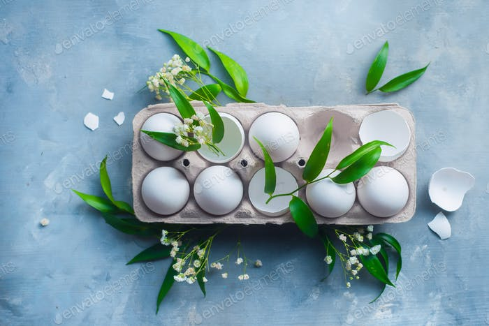 Header with a package of white eggs and Easter decorative green leaves and spring flowers. Modern