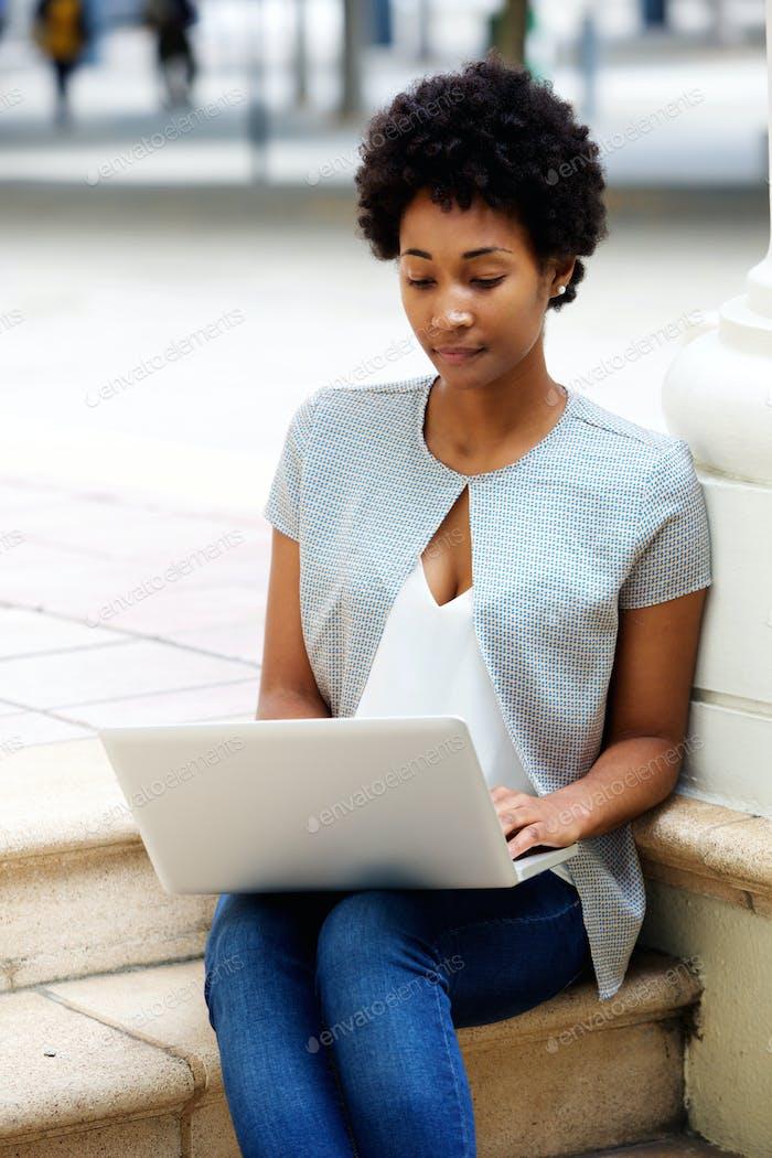 Junge Frau sitzt draußen arbeiten auf Laptop