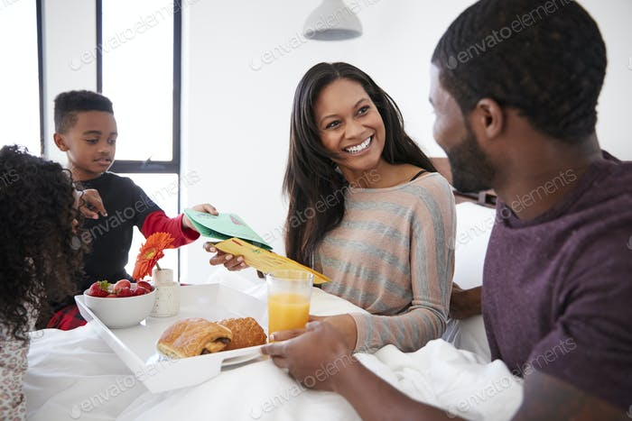 Children Bringing Mother Breakfast In Bed To Celebrate Mothers Day Or Birthday