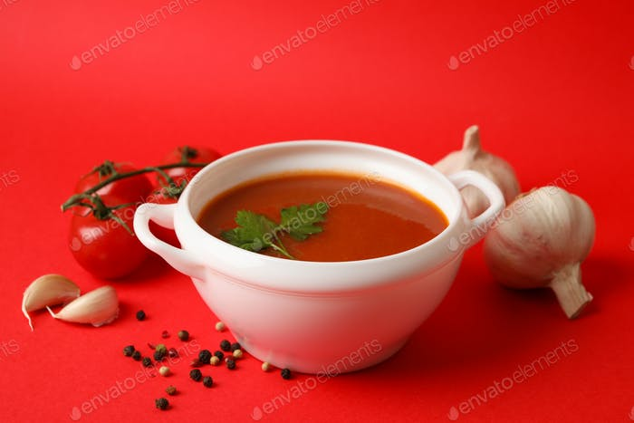 Bowl with tomato soup and ingredients on red background