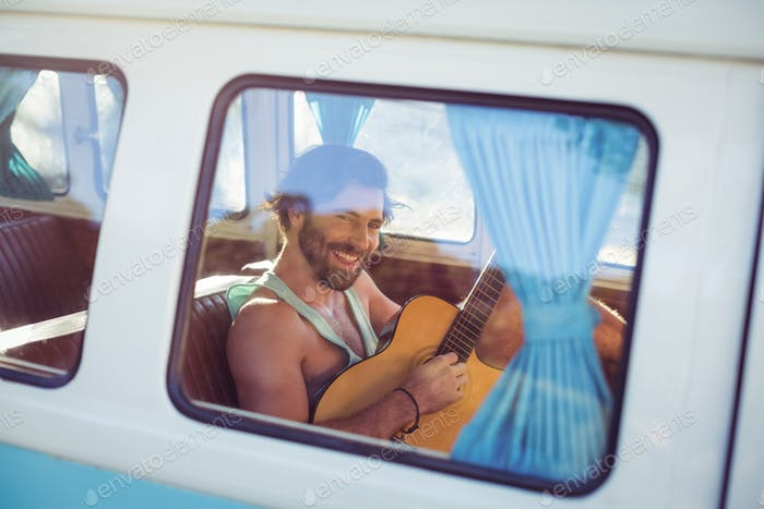 Man playing guitar in campervan