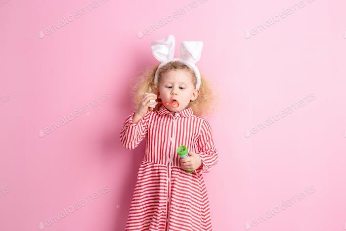 Hübsches kleines Mädchen in einem gestreiften roten und weißen Kleid und Hasenohren auf dem Kopf bläst Seifenblasen auf