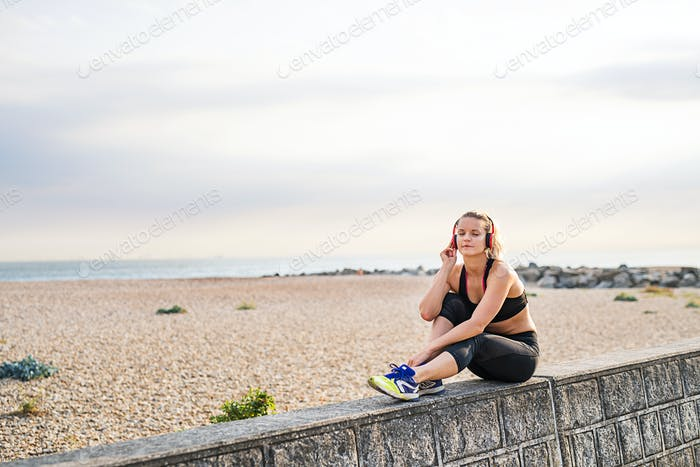 A young woman runner with headphones resting outside by the sea.