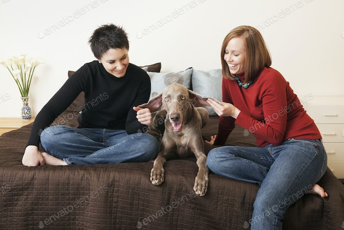 A same sex couple, two women posing with their weimeranar pedigree dog between them.