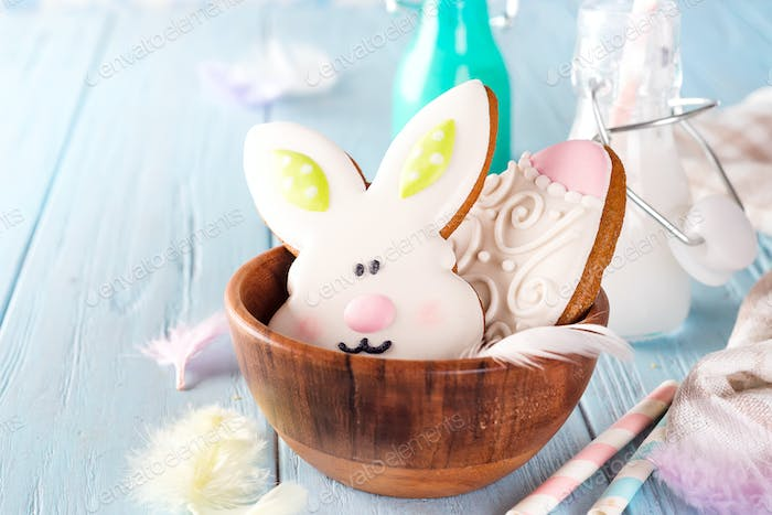 Colorful easter bunny cookies in bamboo bowl on blue wooden background