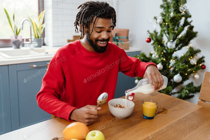 Joyful african american man smiling while having breakfast