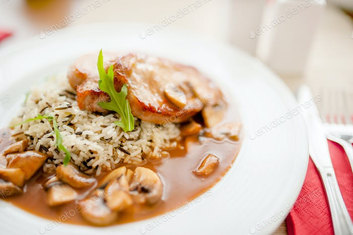 Juicy,  suculent grilled pork chops with mushrooms and rice as m