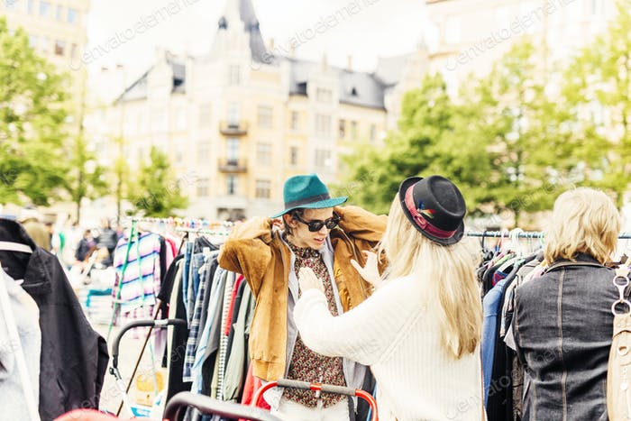 Un amigo que ayuda a un joven en el uso de chaqueta en el mercado de pulgas