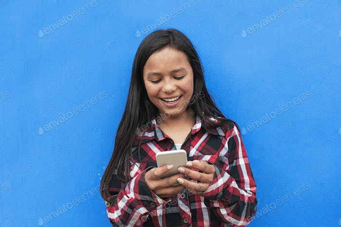 Portrait of cute latino girl using the mobile in the street.