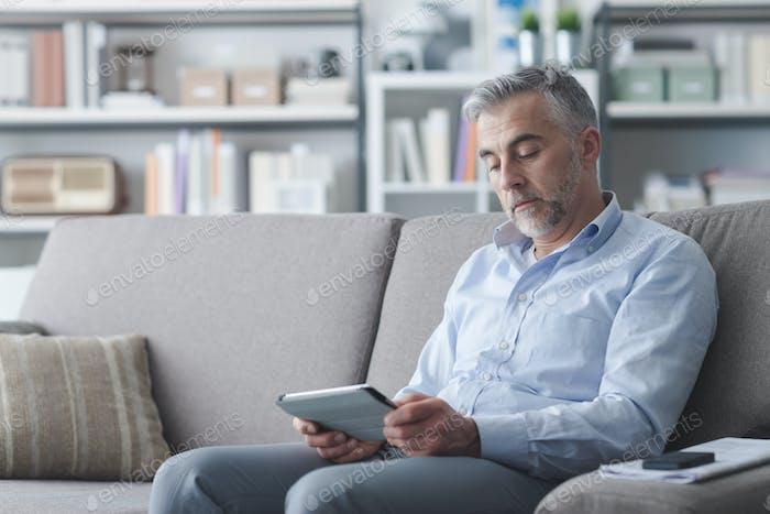 Человек с помощью планшета с сенсорным экраном