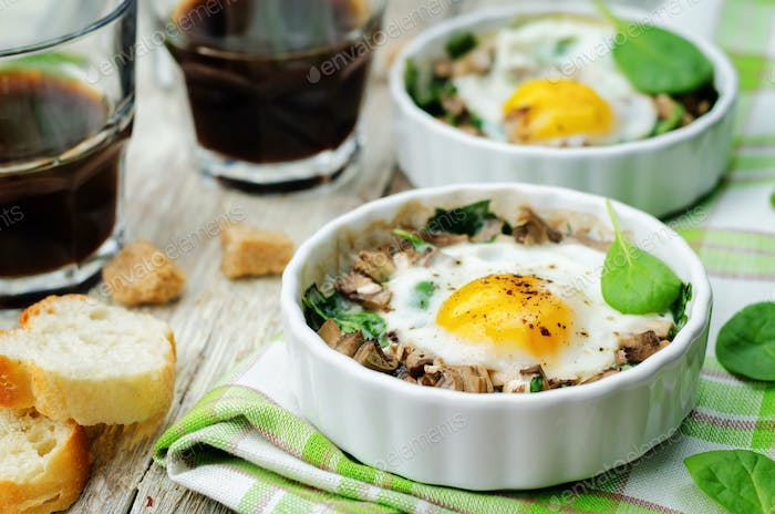 Spinach mushrooms baked egg on a wood background