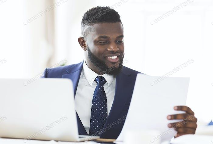 Lächelnd African American Geschäftsmann Überprüfung Berichte in modernen Büro