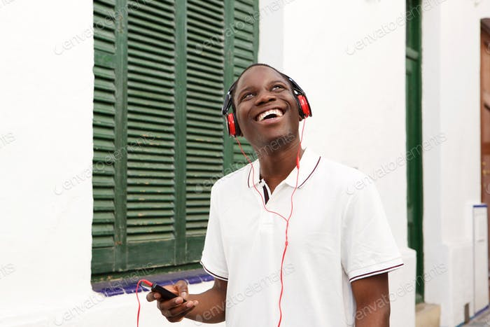 miling young man listening to music with mobile phone and headphones outside