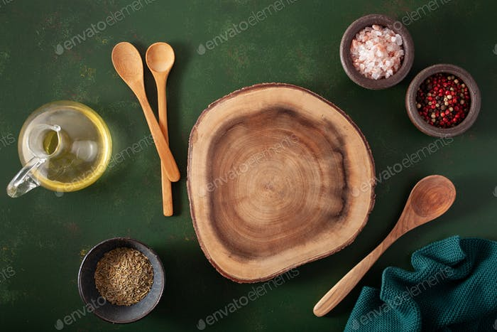 empty serving board salt pepper spoon on green background