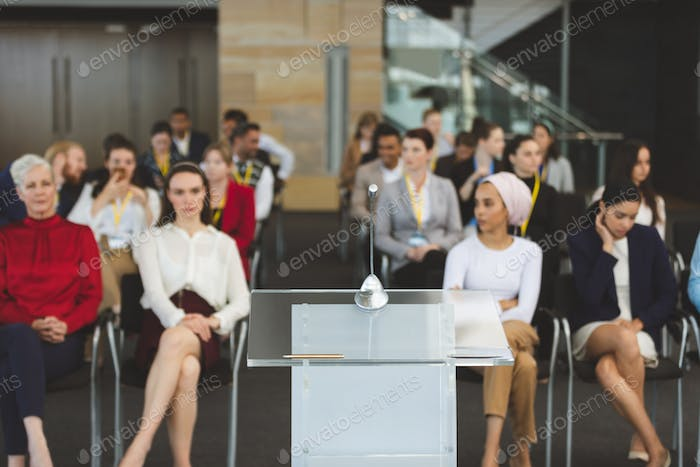Front view of group of diverse business people attending a business seminar in office building
